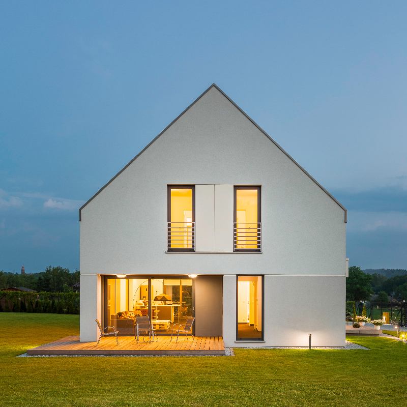 Simple form house located in green landscape, night view